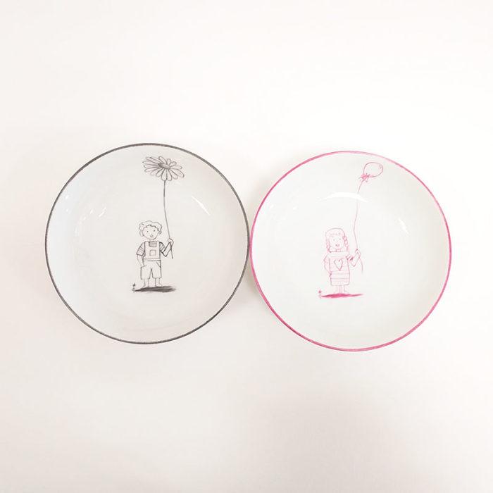 Duo d'assiettes en porcelaine fille au ballon et garçon à la grande fleur. Peint à la main